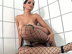 Get hard and become turned on witnessing what Eve Angel is doing in this softcore scene. The heavenly girl stays in fishnet stockings before playing with her wet twat.
