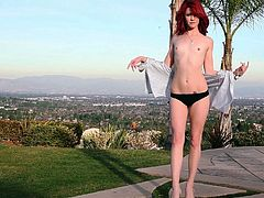Amazing redhead Playboy model poses for the camera outdoors. She shakes her nice ass and then takes the clothes off. Later on she shows her pussy standing on all fours.