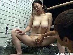 Big-breasted Japanese skank is having fun with her man in a bathroom. They play with each other's privates and then the dude fucks the slut's cunt from behind.