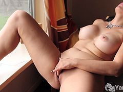 Jade Winders sits on a chair with her legs spread in front of a open window. She rubs her clit until she cums.