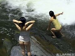 Two salacious Japanese girls are playing lesbian games outdoors. They kiss and pet each other in a pond and then demonstrate their pussy-licking skills.