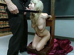 She has a ball gag in her mouth and clamps on her nipples. This blonde babe is tied to a cross in the priest's office and gives him the perfect opportunity to make her suck on his dick. He pushes his penis into her sinful mouth and makes her give him a divine blowjob.