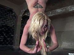 Sexy blonde Samantha Sin allows some guy to put her into fetters in a basement. The guy tortures the hottie and then drills her vag with a big realistic dildo.