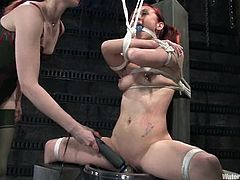 Pigtailed redhead slut Sabrina Sparx is having fun with some dominant bitch in a basement. The mistress puts Sabrina into irons and rubs her cunt with a dildo.