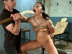 This young babe has a huge dildo shoved into her throat. The dildo is attached to a huge pole that her master is holding. The rope around her arms and chest is tied to the ceiling. She is made to sit on a sybian then she gets her pussy played with.