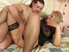 Kinky dude lies behind a lustful blond mature BBW in sheer black lingerie and stockings. He hand strokes her delicious tight pussy before inclining to it for tongue fuck.