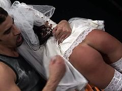 Kinky girl in bride's dress is hogtied in standing position wearing mouth gag. She gets whipped hard in the beginning of the session. Then her pussy hole is fingered intensively.