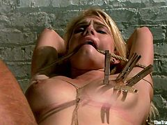 Blonde teen Allie James is tied up with rope and her legs are spread. She has clothespins attached to her pussy lips and all over her tits. Her sex master takes a electric prod to her clit and gives her a nice shock.