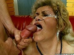 Raunchy granny with fat ass and hairy clam is wearing tight corset filming in hardcore old young fuck scene. She bends over the couch getting banged hard doggy style. Horny dude that is half of her age drills her bearded clam deep from behind. Later he cums onto her ugly face messing it up with huge load.