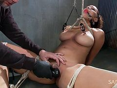 Serena is tied up in crazy positions by her sex master. Her legs are spread wide open and her mouth has a ball gag in it. She gets nipple clamps that are hung from the ceiling, attached to her, and her master takes a big vibrator and uses it on her vagina. Her head snaps back as she is about to cum.