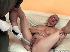 Filthy blond MILF widens her legs while sitting on the couch as a kinky dude drills her soaking bald punani with a thick end of baseball batt in steamy sex video by 21 Sextury,