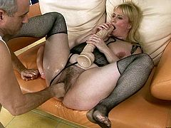 Dirty mature wench Beverly with hair cunt is lying on a couch with her legs wide open. Perverted dude screws her mound with giant sex toy stretching the hole wide as hell.