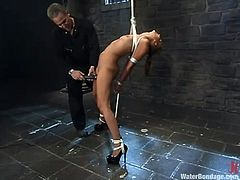 Sexy bitch Isis Love allows some dude to tie and hang her up in a basement. The man toys Isis's vag and then tries to drown the hussy in a glass box filled with water.