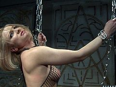 Skanky blond MILF in seductive fishnet bodystocking gets suspended with a metal chain to the ceiling before an insatiable domina blindfolds her eyes and mauls her cuddly body in BDSM-styled sex video by 21 Sextury.
