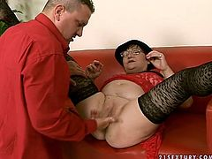 Posh is wearing lacy red dress, hat and black stockings. She sits on a couch spreading her legs wide apart. Perverted man fingers and toy fucks her cunt so she moans wild.