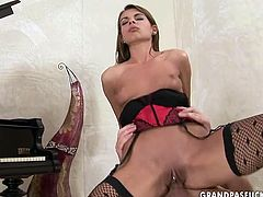 Jaw dropping brunette hottie with a doll face in steamy red and black lingerie and fishnet stockings bends over a grand piano with her leg pulled up while an insatiable dude pokes her cunt from behind before she rides him reverse.