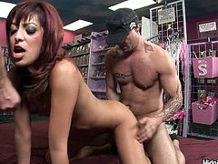 Naughty red haired chick with small tits is fucking in the shop in front of voyeurs. So she gets pounded hard in her twat in doggy position while sucking another hard dick deepthroat.