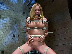 Superb blonde girl lies on a bed being tied up. She gets her wet pussy toyed rough. Then she also gets her nipples tortured with special bondage devices.
