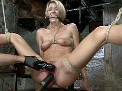 Beautiful tall blonde Amanda Tate is having a good time with some dude in a basement. She lets the guy undress her and then gets tied up, suspended and fucked with a dildo.