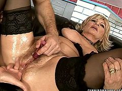 Lewd blond mature goes furious when it comes to sex. She lies on her back wearing steamy black lingerie with legs wide open while an aroused daddy strokes her soaking bushy twat with vibrator.