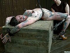 This babe covered in colored tattoos gets an iron net on her face first, while her master belts her down. Then he hogties her and suspends her higher to slap that ass!