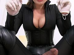 Clothed mistress with big tits plays with her slave's cock