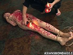 This Asian whore is tied up like the dirty slut that she is. Her master is going to punish her with hot candle wax. He drips the red candle wax on her tits, stomach and legs. She writhes in pain as the hot wax hits her body and hardens on her skin.