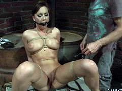 Bosomy brunette hottie gets bandaged by insatiable dude before he plugs her mouth with a gag and starts pinning it with a spiked metal roll in BDSM-involved sex video by 21 Sextury.