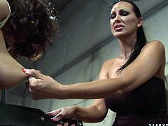 Full lipped brunette domina bandages a slender brunette amateur with a thick rope before she forces her widen her legs to poke her cunt with a dildo in BDSM-involved sex video by 21 Sextury.