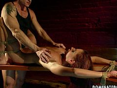 Rapacious master forces a salty red-haired babe lie on wooden table bandaged before he starts pounding her shaved vagina with a sex toy in BDSM-involved sex video by 21 Sextury.
