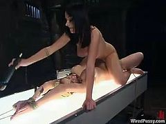 The busty blonde will be tied up and strapon fucked by the kinky brunette who will then do some face sitting on her.