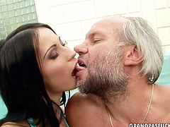 Fuckable brunette slut hooks up with a grey-haired bearded daddy in the pool. She sits on the margin of the pool with legs wide open allowing him tongue fuck her shaved cunt before she pays him back with a blowjob.