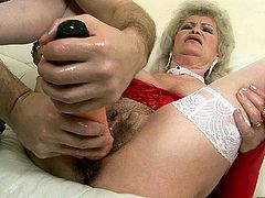 Hot blooded granny with ample frame covered with passionate red lingerie and white stockings lies on her back getting her bearded pussy drilled with different sex toys.
