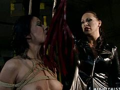 Steamy brunette mistress bandages a salty brunette squeezing her tits tight before she proceeds to slapping her ass with a lash in sultry BDSM sex video by 21 Sextury.