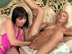 Ruined red-haired mature lies on her back on a luxurious bed while an insatiable brunette lesbian fists her oily cunt before the former stands above her to continue getting fisted.