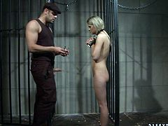 Imprisoned blond prostitute kneels down in front of a horny supervisor to give him a blowjob through the bars of her cage with a collar on her neck and hands cuffed in BDSM sex video by 21 Sextury.