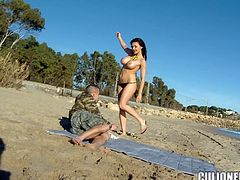 Busty brunette bombshell Aletta Ocean is having fun with some guy on a beach. She sucks his dick devotedly and then they bang in cowgirl position on the sand.