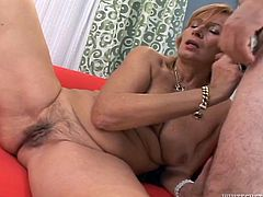 Provocative mature woman seduces the guy appearing half naked in front of him. He slips down her bra suckling her nipples. Then she kneels down sucking his prick. A bit later, horny dude enters wet clam missionary style.