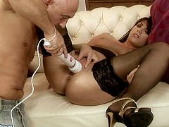 Salty brunette MILF lies on her back with legs wide open wearing lacy black stockings while a voracious bald daddy stimulates her shaved cunt with vibrator in peppering sex video by 21 Sextury.
