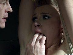 Short haired manlike blond chic gets suspended to the ceiling with one leg pulled up while a perverse dude plugs her mouth and pinches her nipples with fingers in BDSM sex video by 21 Sextury.