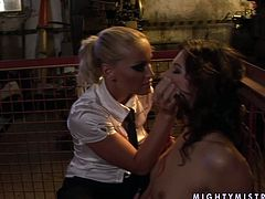 Poor brunette chick is tied up in a small cage. Her legs and hands are spread wide leaving her in vulnerable position. So blonde mistress is playing naughty sex games with her submissive lover.