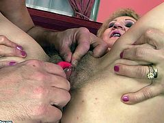 Flamboyant blond mature moans with pleasure while a kinky grey-haired daddy stimulates her bearded pussy with dildo and vibrator simultaneously and later fucks it with his slim fingers.