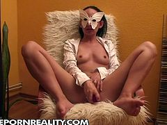 Amateur black haired bitch in mask fists her wet cunt on the armchair