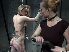 Slender short haired blond bitch stands still with her hands enchained wearing fishnet bodystocking while an insatiable domina slaps her body with a lash in BDSM sex video by 21 Sextury.
