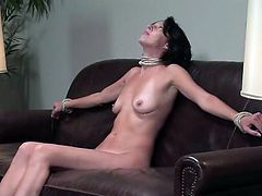 Sexy brunette Victoria K strips and allows some guy to tie her up to a sofa. Then the man rubs Victoria's vag with a dildo and she moans sweetly with pleasure.