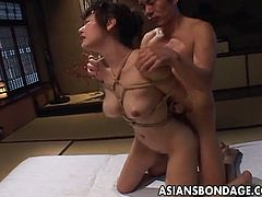 This busty Asian has her hands tied up with rope and her tits are surrounded by ties too. This guy is fucking her moist muff and then he forces her to ride him.