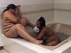 One ebony babe was taking a bath while the other one was keeping her company. She came out of the tub and they ate each others fat pussies on the side of the tub.