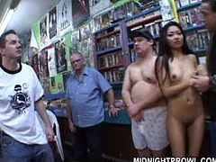 Playful Asian slut with slender stiff body is behaving bad in book store. She stands on her knees in front of a horny daddy to suck his weak penis in front of other aroused dudes in gangbang sex video by Pornstar.