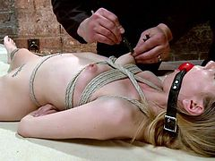 Blonde cutie lays on her back completely naked and tied up. The executor ball gagged her so she won't scream as he fucks her tight, bald snatch. He begins by putting clothespins on her nipples and then grabs a black dildo and a vibrator and fucks her snatch. The deeper and rougher he goes the harder she moans!