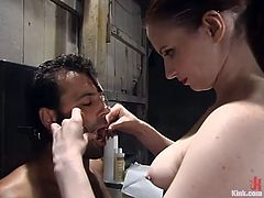 Redhead mistress ties the guy up and pinches his nipples with metal claws. Later on he sucks a strap-on and gets his ass toyed.